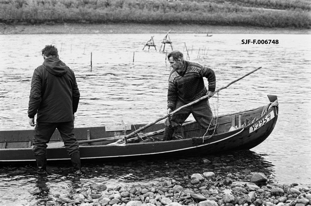 Aslak [med ryggen mot fotografen] og Per Varsi legger et posegarn i elvebåten sin, for å kunne montere dette i en stengselsinnretning de har satt opp med sikte på å fange laks i Tana (Deatnu) i Finnmark.  Bildet er tatt litt sør for bygdelaget Sirma.  På vannspeilet i bakgrunnen skimtes en del staker og et par trefotete stativer, som var forankringspunkter for ledegjerder og posegarn som ble brukt under dette fisket.  Posegarna ble – naturlig nok – montert etter at ledegjerdene, som besto av bjørkeris eller garnrammer, var på plass.  Staven Per var i ferd med å plassere i båten da dette fotografiet ble tatt ble kalt for goarat.  Den var tredd gjennom maskene i posegarets ytre arm.  Denne fiskemåten – buoððu – ble praktisert i sommersesongen, på lavere vannstand og med roligere strømforhold enn under vårflommen i elva.  Fotografiet er tatt på St. Hansaften i 1975.