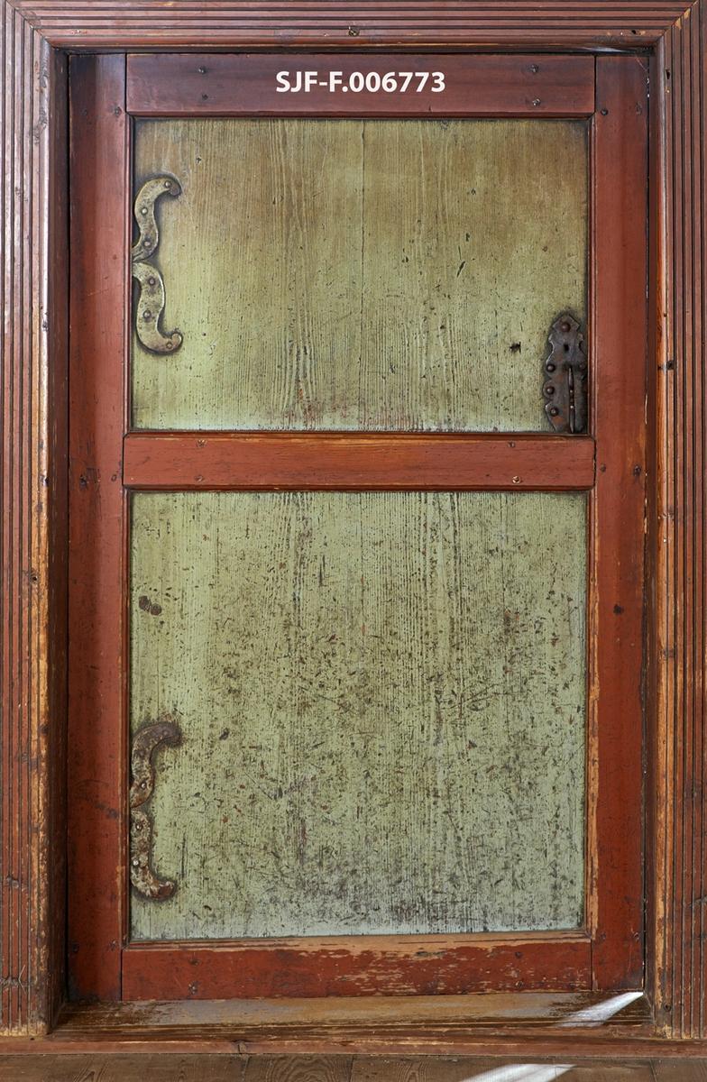Døra mellom stuerommet og sovekammerset i «Austmostua» eller «Østmostua» på Glomdalsmuseet i Elverum.  Denne bygningen er egentlig fra Mogrenda på Vestsida i Hoff i Solør, men den ble demontert og gjenreist på museet i 1919.  Dette er ei fyllingsdør med to såkalte speil.  De horisontale rammetrærne er tappet inn i de vertikale, og forbindelsene mellom dem er låst med trenagler.  Disse komponentene er innsatt med rødbrun maling.  Trespeilene som fyller de to rommene mellom rammetrærne er planhøvlete.  De er innsatt med et tynt grågrønt malingslag, men vi aner likevel årringstrukturen i underliggende ved.  Døra har to hengsler, som later til å være ført gjennom rammetreet mot venstre dørkarm.  Hver hengsle har imidlertid også to S-formete blader som er naglet til hvert sitt dørspeil.  På motsatt side av dørbladet finner vi et låsblikk med et profilert bøylehandtak.  Fotografiet viser også dørterskelen, samt brunmalt belistning med høvlet stripemønster.  Vi vet ikke sikkert om denne døra har fulgt bygningen fra dens tidligste år i Solør, men stilmessig sett harmonerer den godt med bygningskonstruksjonene.    I 1782 foregikk det en dølgsmålsfødsel på Velstu Austmo, muligens i denne bygningen.  Fotografiet er tatt som illustrasjonsforslag til en artikkel som tar utgangspunkt i denne saken, se fanen «Historikk».