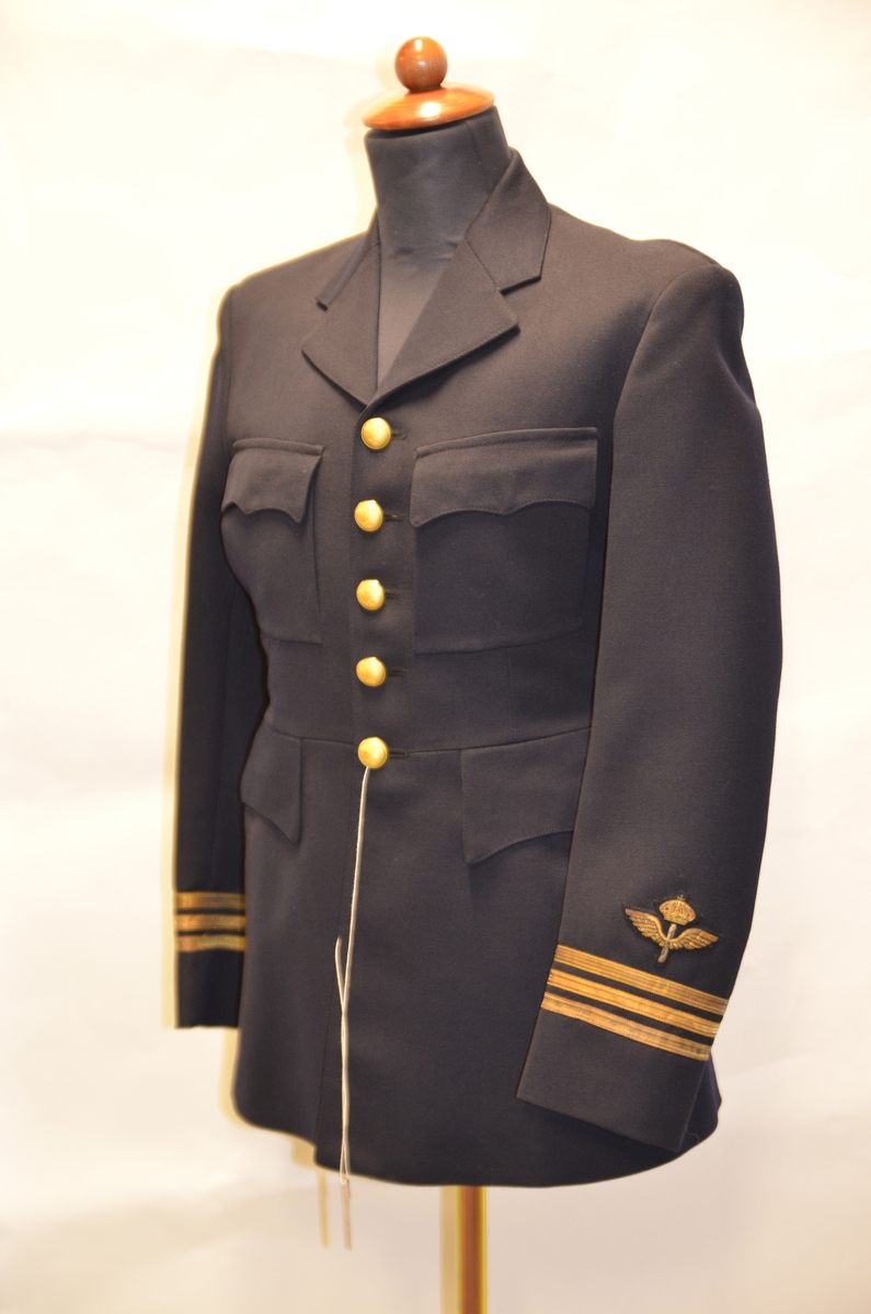 Vapenrock m/30 kapten. Vapenrock  av mörkblått ylletyg. Rocken har femradig knäppning och är för Kaptens grad. På ärmändarna sitter flygvapnets 70mm emblem.