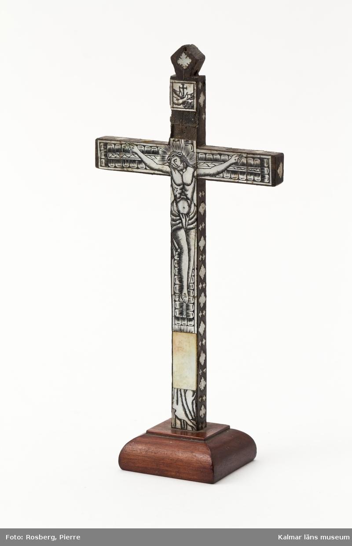 KLM 7961. Krucifix av trä, ebenholtz och ceder?. Den korsfäste och därunder Maria (saknas), därutöver språkband (saknas), överst symbol med två korsade händer med kors, Franciskanernas emblem. Inläggningar av pärlemor, den korsfäste Kristus och små rutformiga stjärnor. Fot av mahogny. Ursprungligen från Jerusalem, ett sk Jerusalemsarbete.