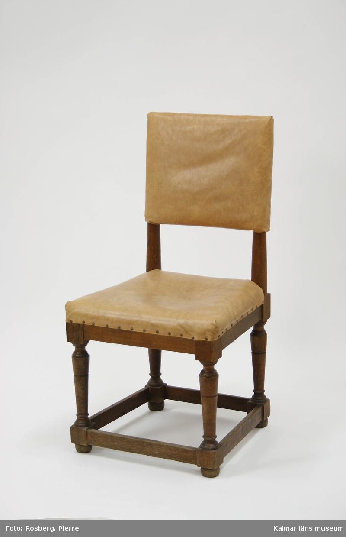 KLM 44912:3. Stol. Av ek med rektangulär ryggbricka, stoppad sits, svarvade ben med ramslå. Stolen är omklädd. Klädd med skinnliknande material, eventuellt galon. 1700-tal, barock stil.