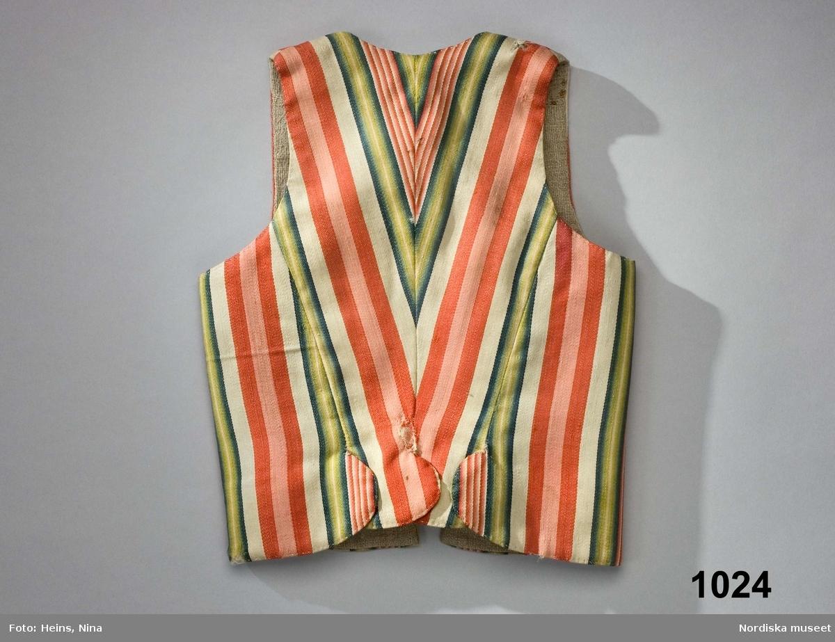Livstycke i 1700-talsmodell av randig kalmink, ett fint helylletyg av kamgarn i satin, varprandigt i rött, rosa och schatterade gröna nyanser på vit botten. 2 framstycken/sidstycken med rundade slitsar fram tränsade med vit tråd, 2 smala ryggstycken avsmalnande nedåt i runda skörtflikar som ligger överlappande. Snörning fram med 5 par tränsade snörhål och en remsa av ljusbrunt sidenchiffon som snörband. Snörningen döljs under en bröstlapp av tyget skuren i två sneddade våder så att ränderna bildar V-form med en nedåtgående snibb. I bröstlappen 4 insydda träspröt för att ge styvnad. Fodrad med grov oblekt linnelärft. /Berit Eldvik 2007-12-17  Livstycket är i liknande modell som rött kamlottlivstycke 1016 använt av samma ägare till bruddräkt 1795. Om detta liv använts runt 1780 bör ägaren då ha varit en mycket  ung flicka. Kalmink var ett dyrbart köpetyg som inte vanligen användes till barn och unga utan mer hörde till brud-och ungmorsdräkt, därför kan det finnas anledning att tro att det snarare bars i samband med bröllopet 1795. Eftersom det bars olika kläder som brud och som ungmor kan båda livstyckena ha använts vid samma bröllopsfest. /Berit Eldvik 2007-12-17