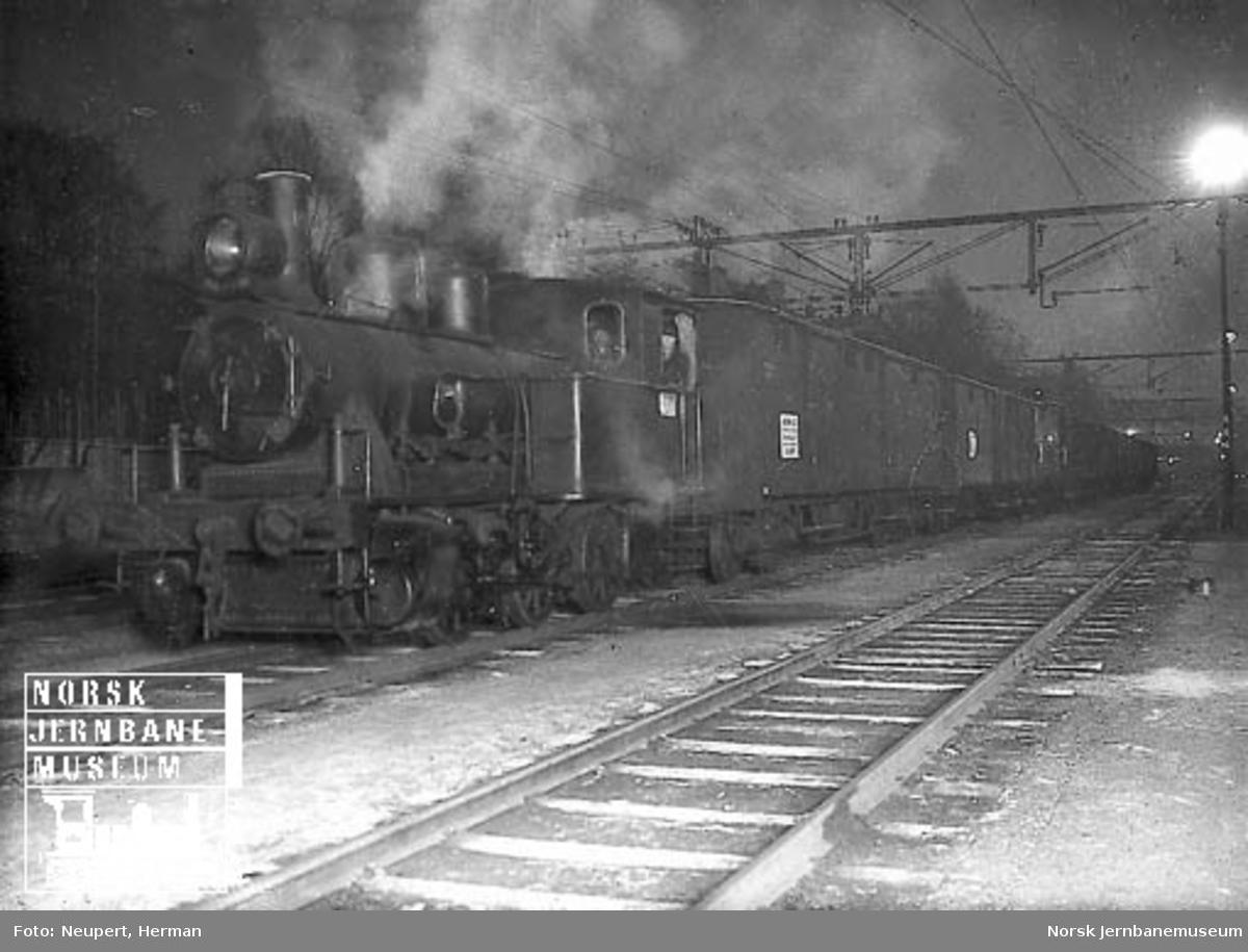 """Kveldsbilde med et damplokomotiv av type 25a foran en lang godsvognrekke; de fremste vognene er merket """"Union Co."""""""