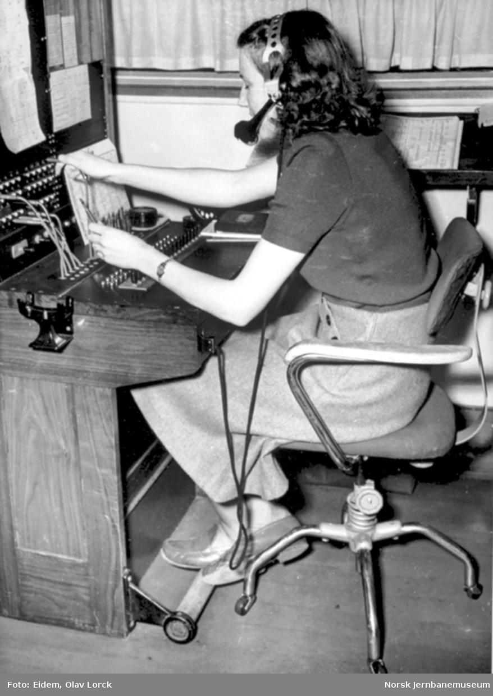 En dame betjener telefonsentralen på NSBs reisebyrå i Oslo