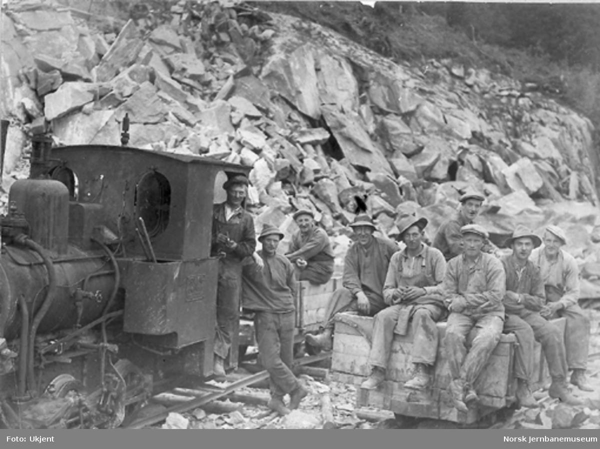 En gjeng anleggsarbeidere fotografert ved et anleggsdamplokomotiv og en tralle