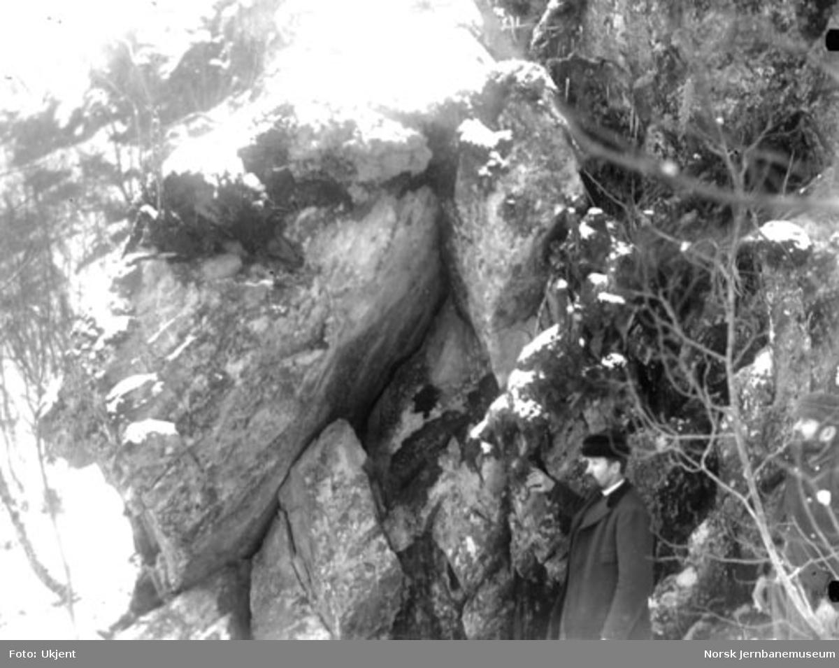 En mann peker på et løst fjellparti