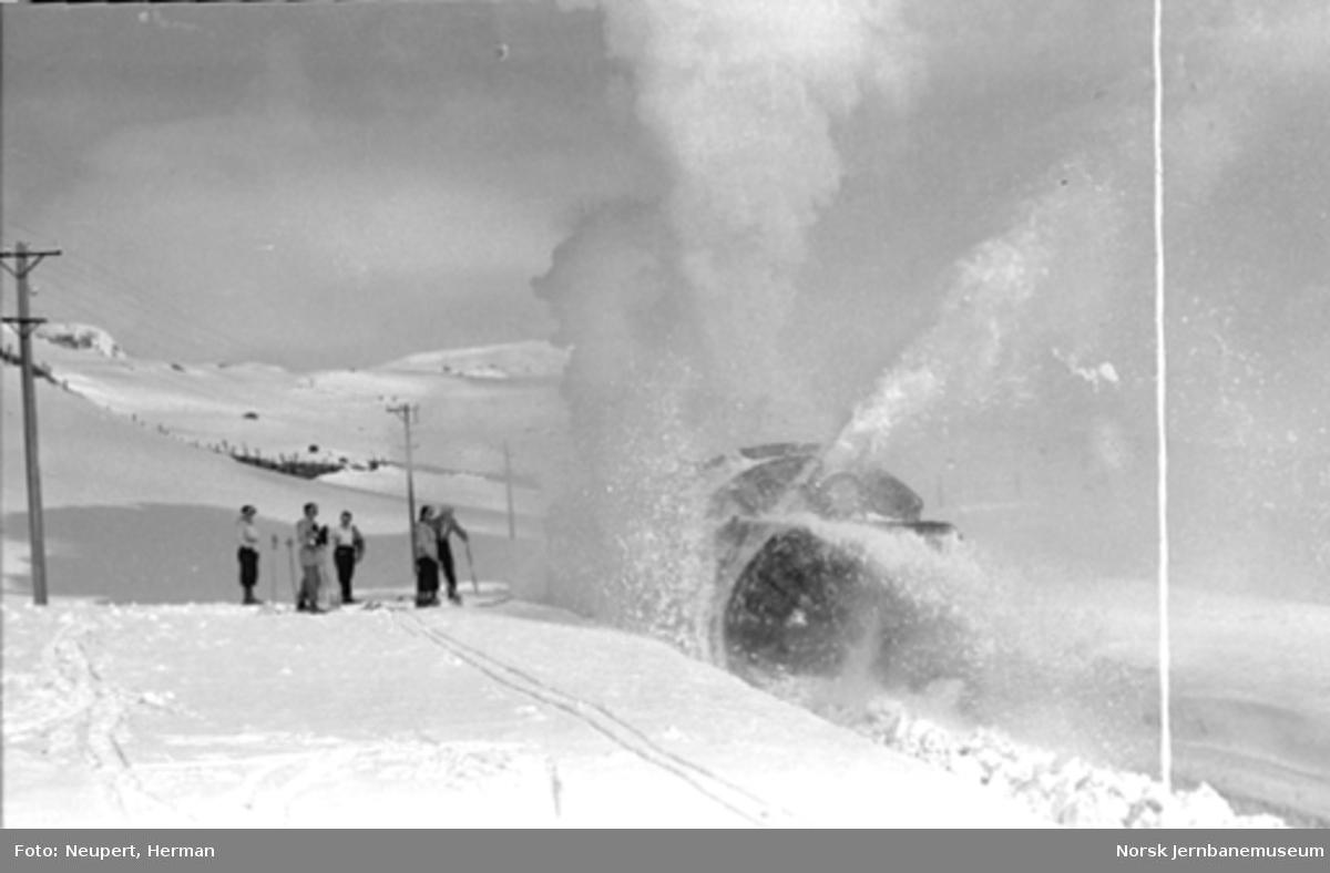 Skiløpere ser på roterende snøplog i aksjon på Bergensbanen