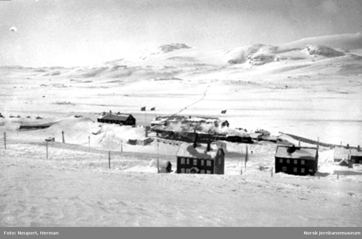 Oversiktsbilde med Finse stasjon og hotellet med Hardangerjøkulen i bakgrunnen, tog på stasjonen.