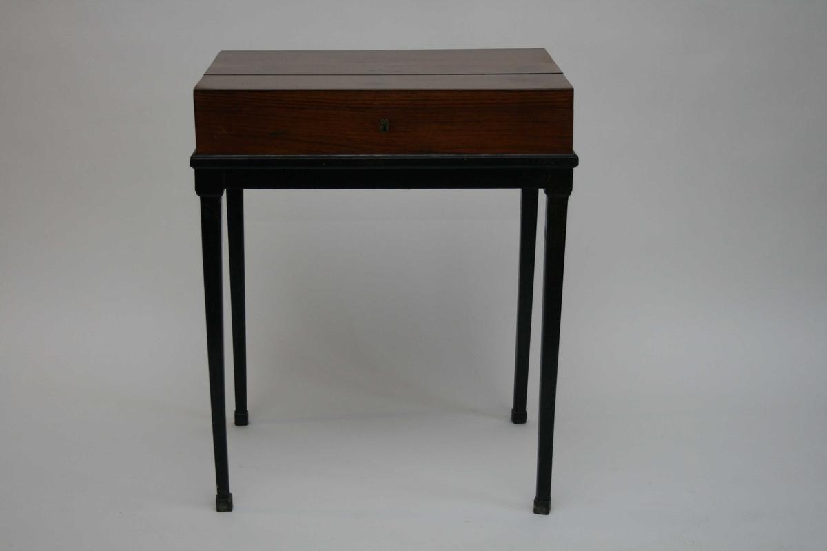 Et av to konsollbord i mahogni. Bordplata kan åpnes og bordet fungerer også som et skrin. Sarg og bein er malt svart.