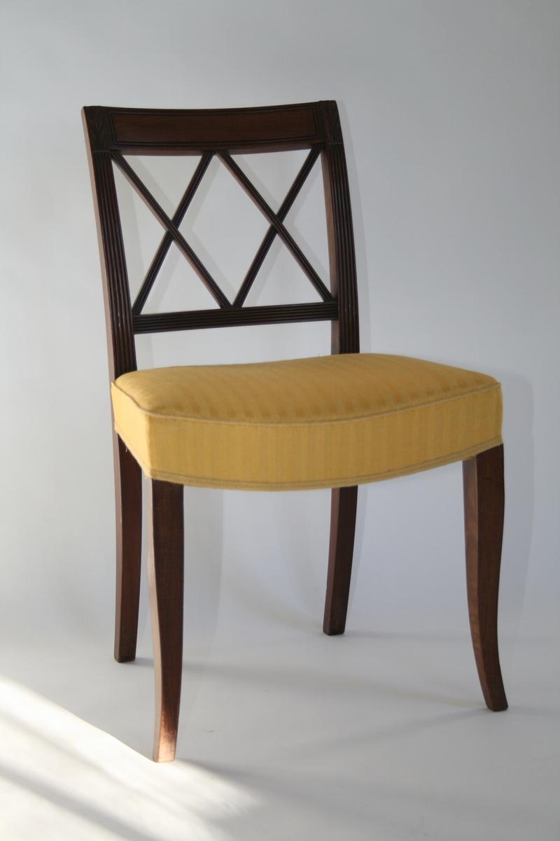 En av 8 like stoler i mahogni. Ryggbrett med spiler i to diagonale kryss, og riller. Stoppet sete trukket med gult  stoff. Trekket er sekundært (1960-tall)