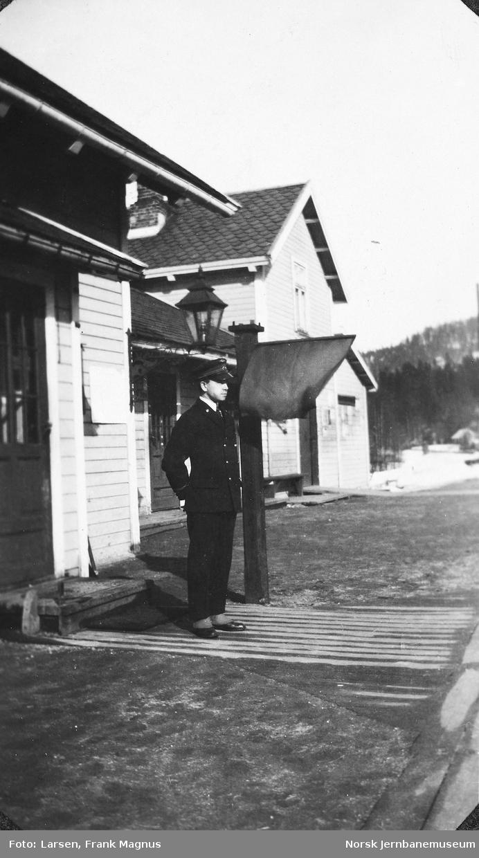 Telegrafist Frank M. Larsen på Sandermosen stasjon med oppsatt flagg