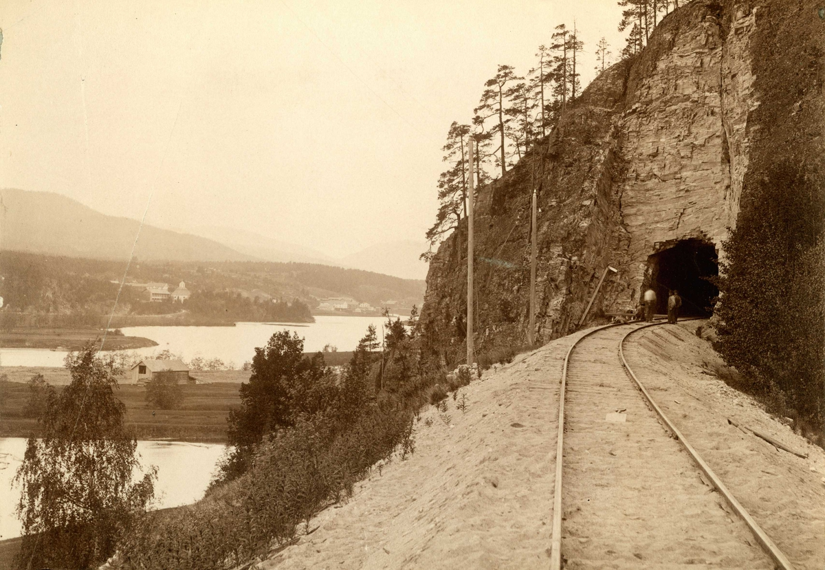 Koppang, Stor-Elvdal, Sør-Østerdalen, Hedmark. 1890-årene. Arbeidere på jernbaneskinna foran tunnel. Utsikt over Glomma.