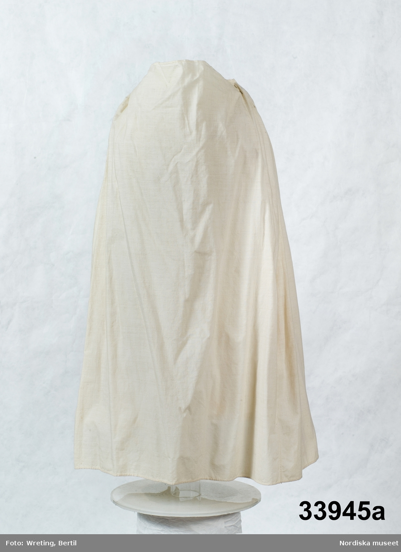 """Katalogkort finns.  Bruddräkt bestående av a. kjol, b:1-2. tröja. c. band.  Kjol och tröja av vit tunntrådig tätvävd bomullslärft   b:1. Tröja, kort med skört i sen 1700-talsmodell.  2 framstycken/sidstycken  och 2 ryggstycken kraftigt avsmalnande ned mot skörtet bestående av 4 veck som hålls samman med några stygn Som dekor vid skörtet två sammanhängansde tofsar av vitt bomullsgarn, gjorda som en """"smällkaramell"""" som lindats på mitten med utstående trådar åt sidorna som bildar tofsarna. Infällda skörtkilar i sidorna. Smal fåll i nederkanten med en rad efterstygn. Isydd ärm med skarvkilar under armen, på axeln 9 lagda veck, rak ärmkant. Vid halsringning, knäppning saknas. Helfodrad med vit linnelärft ned till midjan, skörtet ofodrat. I midjan ripsband i linne smalrandigt i blått och rosa på vit botten, 8mm brett, fastnäst med några stygn på 3 ställen. Knyts fram. Runt detta band är påknäppt 2 sydda band (b:2+) av bomullstyget, 1,5 cm breda försedda med en tygknapp och knapphål i ändarna.. Kan troligen ha knäppts fast runt ärmarna vid handleden. /Berit Eldvik 2008-12-11"""