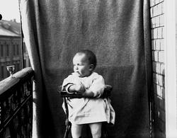 Lillebror Axel Q. Wiborg i barnestol fotografert på balkong,