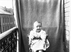 Lillebror Axel Q. Wiborg i barnestol på balkong, ant. Meltze