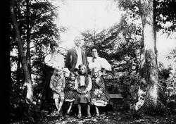 Familiegruppe, fire barn sitter på benk, en mann og to kvinn
