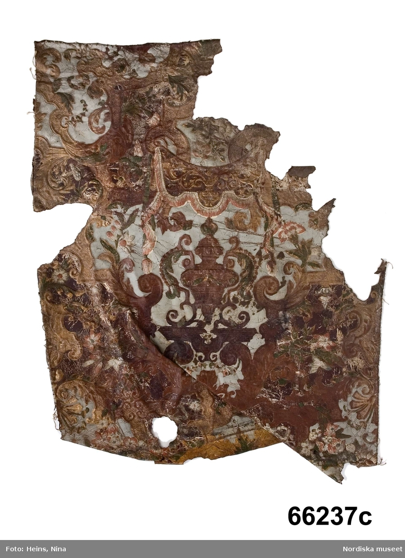 """Huvudliggaren: """"a-h En samling gyllenlädersprof 8 stycken:""""  Katalogkort: """" Ett skinn med storlek 0,84m x 0,62 m. En ränga med storlek 0,82 x 0,17 m. I mönstret ingår ett landskap med en fårahede i förgrunden och en stad i bakgrunden samt Mercurius sväfvande iluften. a,h) Motiv: Hermes flygande över skog och herde med fårahjord. b) Ornamental bit tillhörande landskapstapeten med samma nummer. c) Renässansmotiv, beslagsornamentik, draperimotiv, inslag av silver. d) 105x30 cm. Örn med blad i näbben. e) Liten bit. Stor ros. f) Liten bit med beslagsornamentik. g) Liten bit, grönt och guld. Mönster: putto och blommor. (S.W.)""""  Vid inventering 2007 fördes litt. h över till litt a+ då de har samma motiv. Leif Wallin 2007 Delar har också överförts från inventarienummer 240.008 i samband med inventeringen 2007. Gyllenläder, 32 delar, sannolikt från tapeter. Goffrerade. bemålade, försilvrade och slutligen fernissade. Totalt 32 delar med skilda motiv. Merparten stela och med slitage. Vissa även med revor, veck och hål. a+) Nio delar, på vissa delar figurscener med herde vaktande får, i bakgrunden stadsbild. Ovanför herden Hermes i skyn. Motivet i övervägande grönt, blått, rött och vitt. Inramande ornament med beslag, blommor, blad etc. i guldbrons, rött, brunt och grönt. Vissa delar med marint motiv, båtar på vatten, övervägande i blått, grönt, brunt och vitt. Även dessa med omgivande ornament. Mått som följer: B. 85, H. 61,5 cm., B. 46, H. 54 cm. (tidigare 240.008), B. 39, H. 24 (tidigare 240.008, har suttit ihop med fg.), B. 31, H. 56 (tidigare 240-008), B. 84, H. 21 (tidigare 66.237H), B. 35, H. 58. I en av kartuscherna på denna del, i relief spegelvänd text EGIDEUS IACOB (eller tvärtom) inramande monogrammet IE (?) (tidigare 240.008), B. 71, H. 33 (tidigare 240.008), B. 71, H. 49 (tidigare 240.008), 23,5 x 21,5 (tidigare 240.008). b+) Fem delar. Beslagsornamentik i guld och brunt, urna under baldakin samt blommor och blad i vitt, rosa, och grönt, ljusblå bakgrund. Delarna """