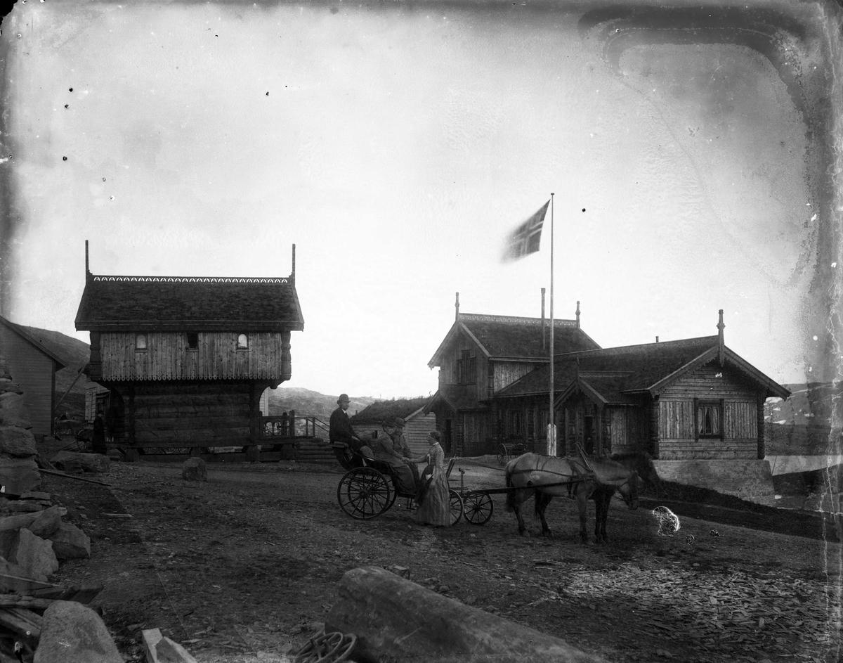 Gårdstun på Haukeliseter i Telemark, med personer sittende i en vogn trukket av to hester. Bygning, stabbur og flagg i bakgrunnen.