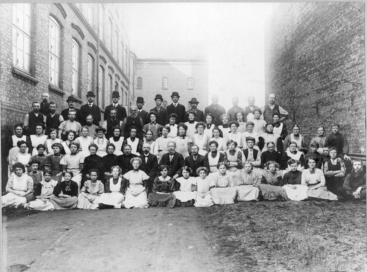 Gruppeportrett, fabrikkarbeidere fra Johannes N. Withs Tobaksfabrikker. Kvinner, menn og barn. Antatt før 1893.
