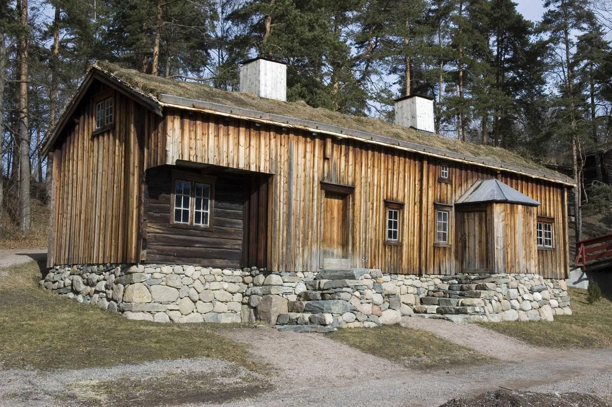 VÅNINGSHUS FRA HOVDE PÅ ØRLANDET, 1700 OG 1850  Overført til museet 1922, gjenoppført 1931   Huset er bygd i to perioder. Den eldste delen, i høyre ende, består av stue og kjøkken, den senere påbygde delen har storstue og masstu (bryggerhus). I to rom er det bileggerovn, en ovnstype egnet til torv, og som særlig var vanlig i trefattige strøk, der torv ofte ble brukt til brensel. Norsk Folkemuseums stue fra Lende på trefattige Jæren (91) har også bileggerovn.   (Tekst hentet fra By og bygd 43,2010)