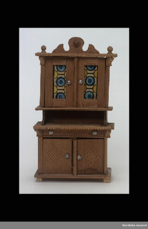 """Inventering Sesam 1996-1999: L 11 cm B 5,6 cm H 20,5 cm Skåp, skänkskåp, till dockskåp, av obehandlat trä. Nederdel med ett par skåpluckor med påklistrad rombformad dekor, ovanför en låda under en skänkhylla. Indragen överdel med ett dörrpar med glasrutor. Bakom glasrutorna plåklistrat papper (imiterande glasmålning). Uppdraget och konturerat krön. Blomformade dragknoppar av tenn. På krönets och skänkskivans framkant påklistrad brun pappersremsa med lövformad nederkant. (många """"löv"""" saknas) På baksidan påklistrade papperslappar, den mindret (som syns genom hål i bakstycket i underskåpet) med tysk text. Tillhör dockskåp inv 164.570. Brukad avgivarinnan född 1886. Leif Walin nov 1997"""