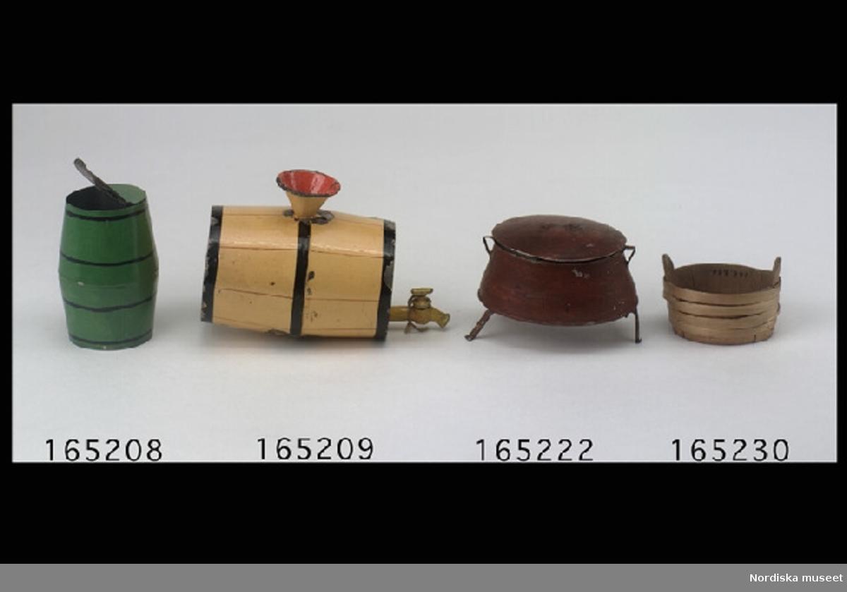 Inventering Sesam 1996-1999: L 10,5 cm (med kran) H 7,5  cm (med tratt) Tunna av bleckplåt, målad i gult med röda ränder (imiterande brädor) och svarta tunnband. På ena kortändan tappkran med vred (fungerande)  och ovanpå tunnan en rödmålad tratt för påfyllning. Undertill märken efter benställning Tillhör dockskåp 165.280 Bilaga Leif Wallin 1996