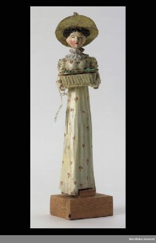 Inventering Sesam 1996-1999: H 21 cm (med sockel) Docka av trä, målad, föreställande dam iklädd gulvit klänning med  glest rött mönster och hög midja, vit krage, stor gul hatt av papp med grön/svart rosett och plym (hattens brätten brutna och färgen krackelerad). Dockan håller en vit korg med fällbart lock framför sig. På locket gröna blad och två blommor i rosa. I korgen ligger ett lindebarn. Dockan är något vridbar vid midjan och vid sockeln. Dockan har metalltråd genom kroppen och har ursprungligen troligen varit mer rörlig. Sockeln är omålad och troligen sekundär. Dockan är en halvautomat, men funktionen har försvunnit. Bilaga Leif Wallin 1996