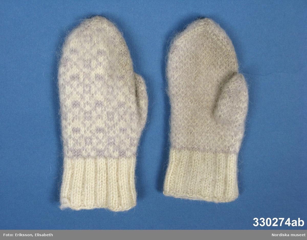 Tumvantar [a-b] i ullgarn för ca 5-årig flicka. Handen slätstickad i vitt och lila med rutmönster på ovansidan. Resårstickad mudd i enfärgat vitt. Anm: Något fläckiga på undersidan. /Zingoalla Rosenqvist 2010-04-08
