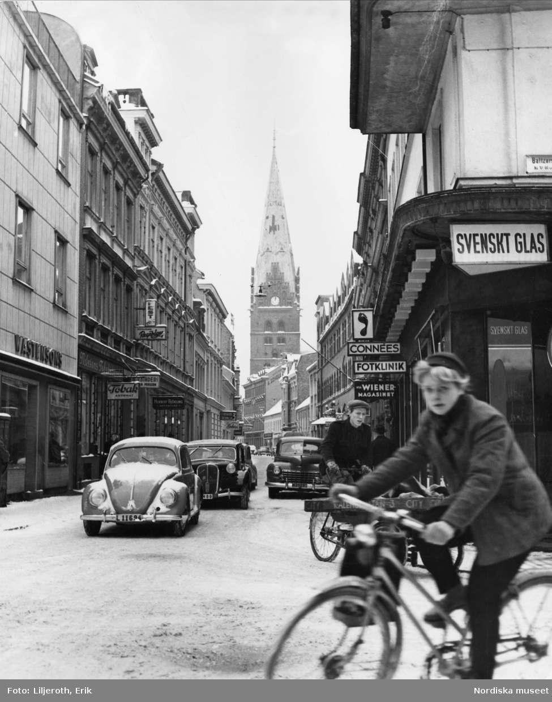 Bil- och cykeltrafik på vintrig stadsgata, Kalendegatan, i Malmö. I bakgrunden syns Sankt Petri kyrkas torn.