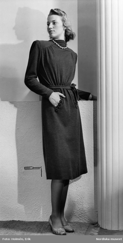Modell i knälång klänning med skärp och pumps. Silverhalsband.