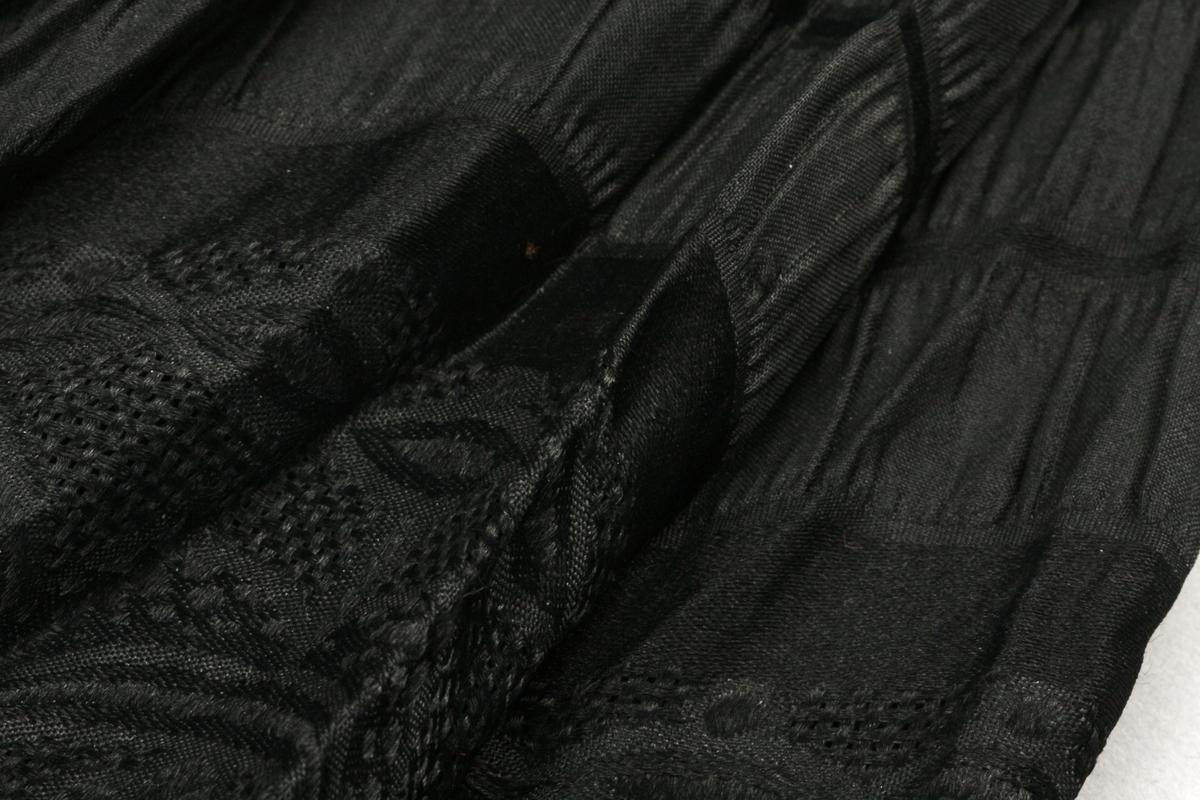 Bred bord øverst. Rynkede og glatte felter i striper. Treskaft med buet håndtak av ruglet plastlignende materiale med 2 halvmåner i sort og hvitt. Metallspiler og tupp