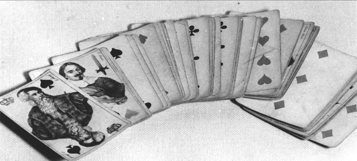 Kortlek med 51 kort. Litograferade och handkolorerade kort. De avbildade figurerna är historiska kungligheter och adelspersoner.