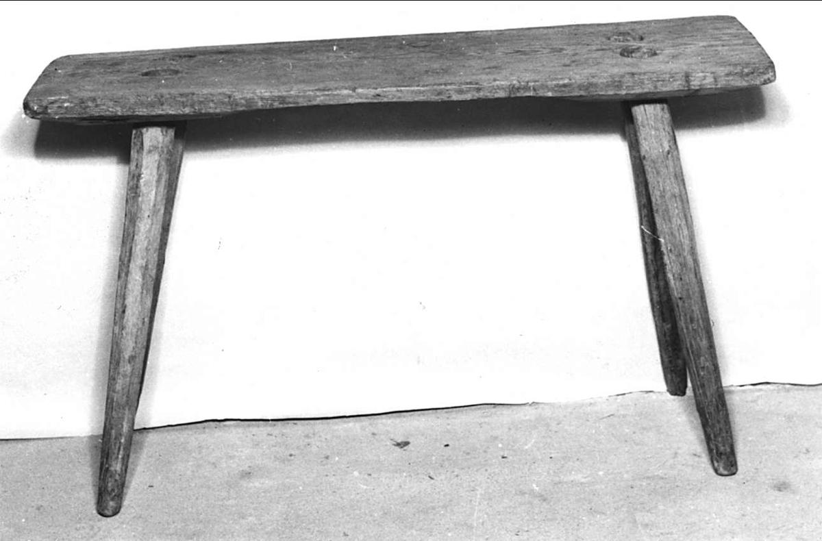 Bänk, säte, av trä. Omålat. Under sitsen inristat: 1864 J. F.