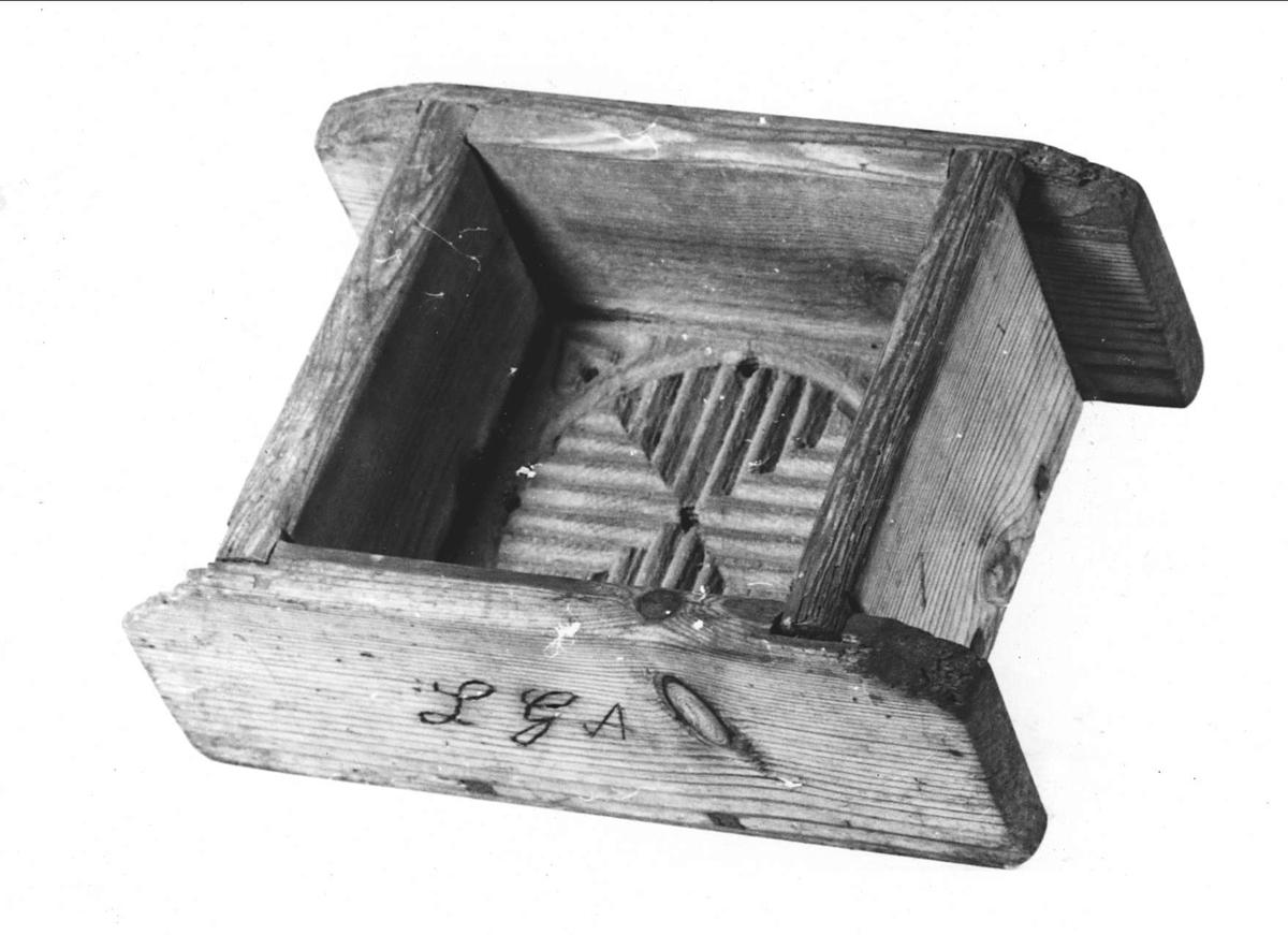 Ostform av trä. Dekorerad med karvsnitt i botten. Inskuret i ena väggen: L G A.