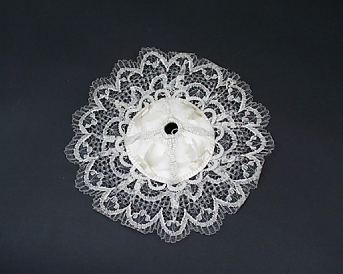 Buketthållare av vit papp klädd med vit tyll och vita rosetter, runt kanten vit spets.
