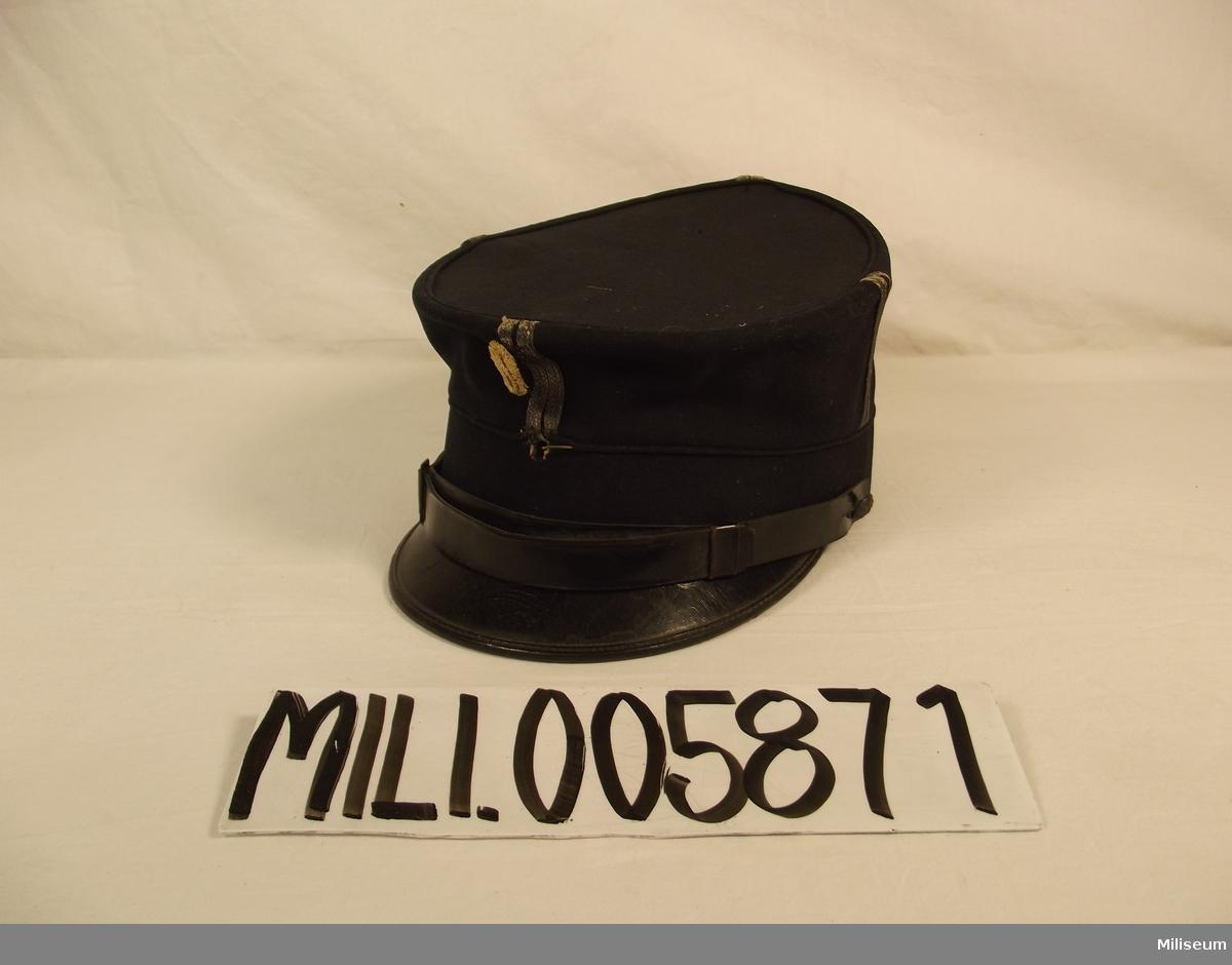 """Mössa m/1865, för fanjunkare vid Intendenturkåren. Har tidigare varit försedd med så kallad """"kringla"""" vilken tagits bort 1899. Mössknappen m/1880 saknas."""
