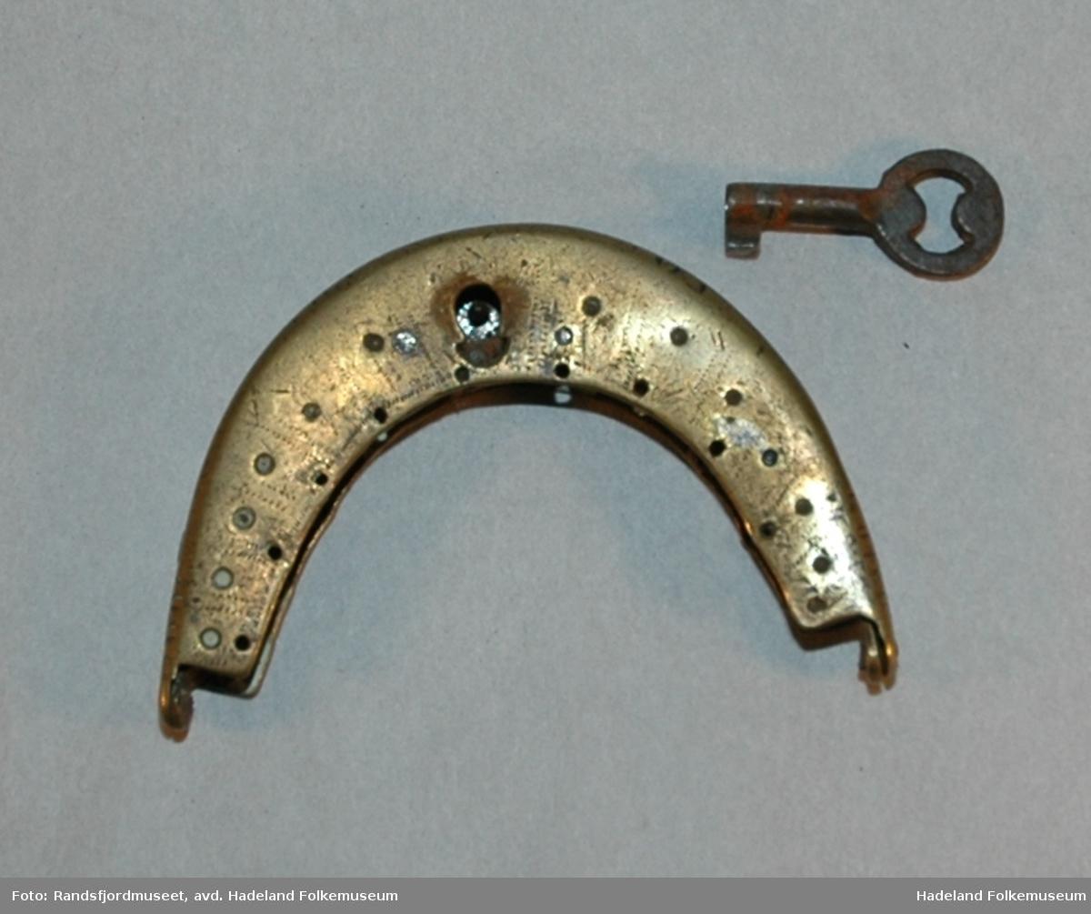 a: Buet lås med ti hull til montering på pung i tekstil/skinn. To deler som er hengslet sammen i endene. b: nøkkel