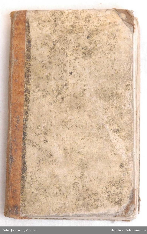 Stiv og brun perm med gullskrift på ryggen, skinnrygg og tekstil på hjørner