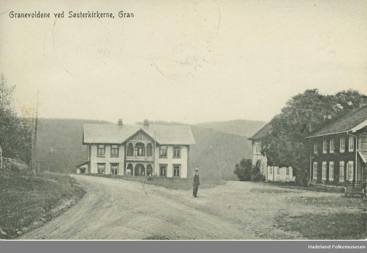 Granavollen med Kommunehuset og Granvolden Gjæstgiveri fotografert fra nord. En mann står midt på vangen. En ser del av kirkegårdmuren på venstre side.