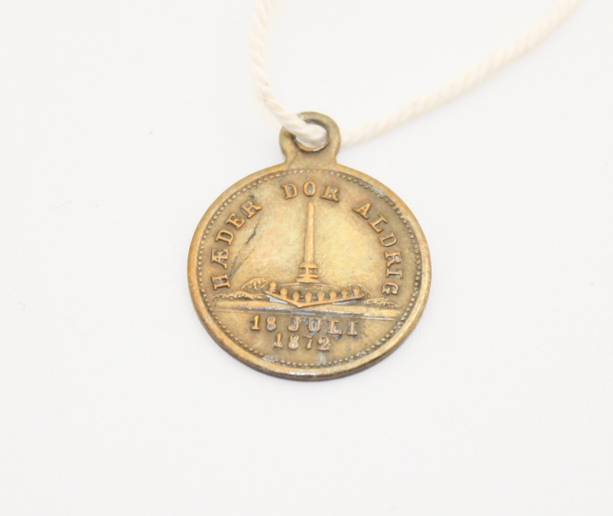 Sirkulær minnemynt med hempe. Mynten er på den ene siden dekorert med et pilkogger, økt og spyd som krysser hverandre. På den andre siden er Haraldstøtta. På begge sider er myntens kanter dekorert med en prikket kantlinje. Denne typen medaljer ble laget av Stavanger By i anledning Tusenårsfesten 18. juli 1872, og avdukingen av Haraldstøtta i Haugesund.