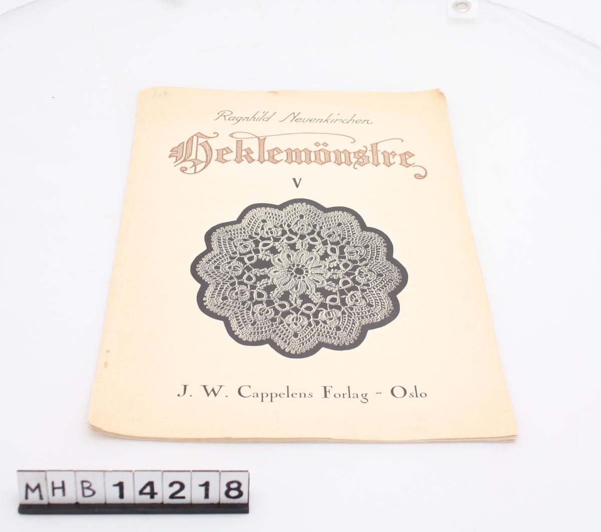 Rektangulær bok med myk pappinnbinding. På fremsiden er et bilde av en heklet  brikke. Boka inneholder hekleoppskrifter og bilder av heklede produkter.