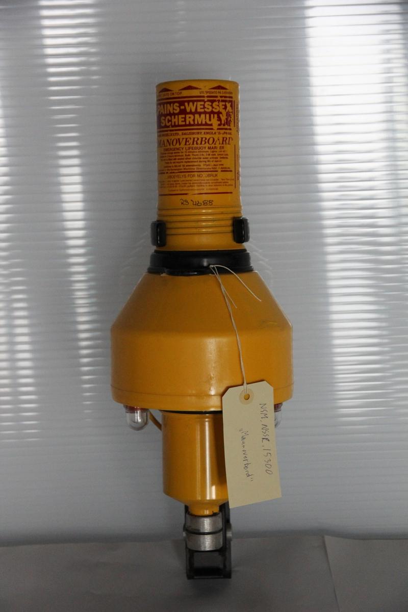 Gul metall og plastikk livredningsbøye i svart metall brakett. Laget for å slippe ut røyksignal ved kontakt med vann.