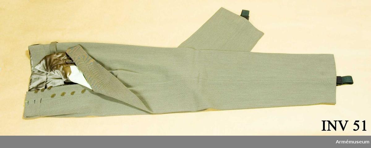 Gråbrungrön diagonal. Livet fodrat med grått siden. Fickfoder i vit bomull. 2 fickor knäppta med knappar märkta: Militär Ekiperings Aktiebolaget.  Hällor av resår, fästade med knappar. Har tillhört Gustav VI Adolf (1882-1973).