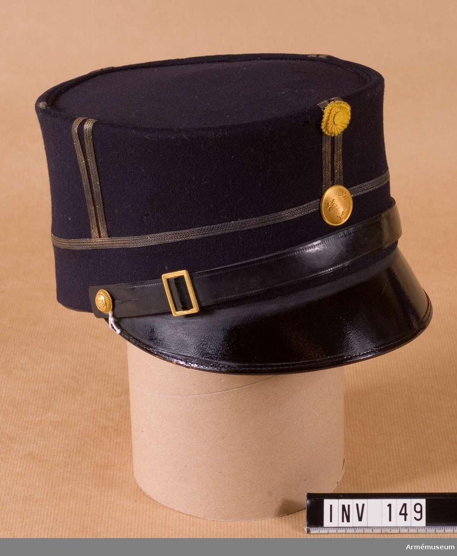 Mössa i mörkblått kläde, samma som livplagget, med skärm och  rem av svartlackerat läder. Två st stolpar av 5 mm galoner i guld. En smal galon (5 mm) runt kullen = gradbeteckning för underlöjtnant. Kokard m/1865 av gult plisserat siden i två  lager, med en överklädd pistill. Kupad knapp m/1865 för  infanteriet (tre kronor) i guld. Kupad knapp, modell mindre, på  vardera sidan = Västernorrlands regementes i guld. Guldfärgat  spänne i mössremmen (13 x 16 mm). Svart sidenfoder. I kullen märkt M.E, Militärekiperings A.B. Svettrem av mellanbrunt  läder, ihopsytt mitt bak med öppen kant. Nedre, inre omkrets: 540 mm. Rem i fixerat läge 340 X 18 mm,  stor knapp diam. 22 mm, liten d:o diam 13 mm.