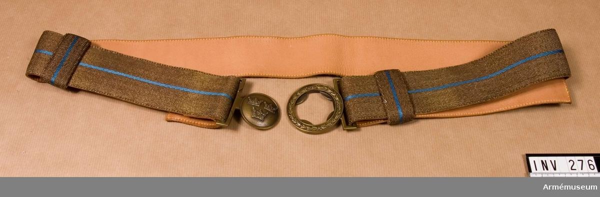"""För officer och underofficer, av gul bronsmetalltråd med en smal rand i mitten av blått silke. Skott med ljust läder. Bronsfärgat spänne med tre kronor, knäppningsdelen bär en lagerbärskrans. Skärpet är ställbart genom spännets enkla skänkel. Viks åt avigsidan och fasthålles med en sölja, 25 mm bred. Söljans blå rand kommer här att stå vinkelrätt mot skärpets. Söljan är skinnskodd med ljust läder. Spännet märkt på """"tre-kronor""""-delens baksida: C O Sporrong & Co Stockholm."""