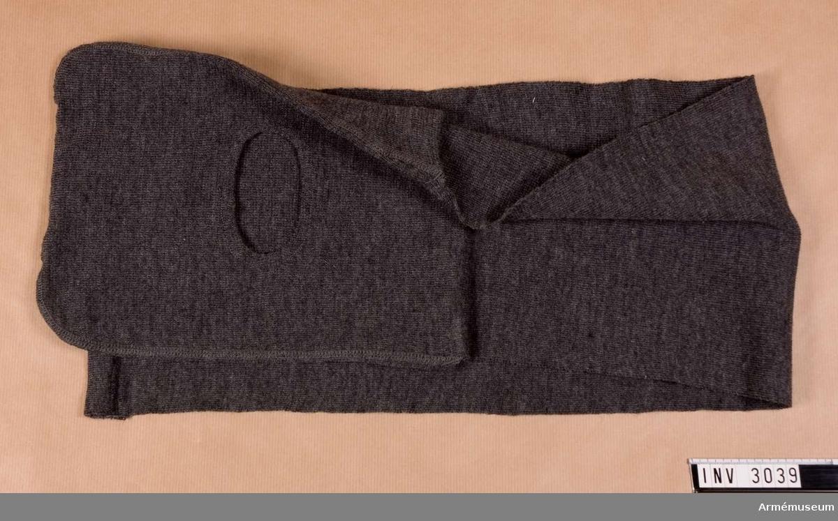Av gråmelerat yllegarn. Vid ena kortsidan lagd dubbel i 260 mm. Ett ovalt hål, 90 mm brett, är upptaget 130 mm från kortsidan och går att sticka huvudet igenom när man har vänt halsduken ut-och-in. Vid kyla används plagget på detta sätt som mössa. Med mantel som halsduk eller under hjälm som huvudskydd.