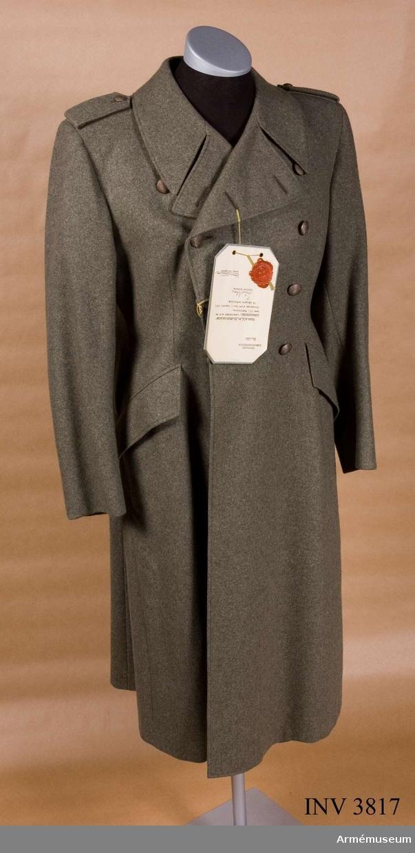 """Av gråbrungrön kommiss eller diagonal. Tvåradig m fem stora  knappar m/1939. Löstagbara axelklaffar. På var axel två  trådslejfar för fästande av axelklaff som knäppes m små knappar  m/1939. Nedvikt krage, slag som kan bäras hop- eller uppknäppta. Sprund i ryggen. Två snedställda sidfickor med raka lock.  Helfodrad m konstsiden. Tjänstetecken: utföres i metall, knappar i bronsfärg,  tjänsteklassbeteckning i mörkblått. Utgöres av stjärnor,  stjärnknappar, stolpar och fyrkantsgalon anlagda enligt  m/1939-systemet. På kragen truppslagstillhörighet. På  axelklaffarna förbandstillhörighet och i förekommande fall tjänsteklassbeteckning. För personal ur SLK, SBS, SRK och  sjuksköterskor tjänstetecken m/1946, stort/litet, i stället f  truppsl.-/förbandstecken. Av metall m vederbörlig organisations  emblem. Lackerat eller i emalj. Vidhängande etikett anger fastställelsedag: """"2 augusti 1946"""". Undertecknat av Torsten Nilsson, chef FÖD och Henry Kellgren, chef FKE."""