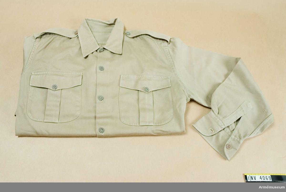 Skjorta m/1961 t tropikuniform. Bomull. Storlek: 50. Tropikskjorta m/1961, beigefärgad. Av beigefärgad  bomullsdiagonal m fast dubbelvikt krage och fasta manschetter,  slits i sidorna. Knäppt mitt fram med sex knappar i nylon. En  knapp i den enkla manschetten. Sydd m fällsömmar. Axelklaffar i  samma tyg som skjortan knäppt med nylonknapp vid kragen.  Material beige (Q) skjorttwills. Användes i tropikerna och vid tjänstgöring FN m.m.