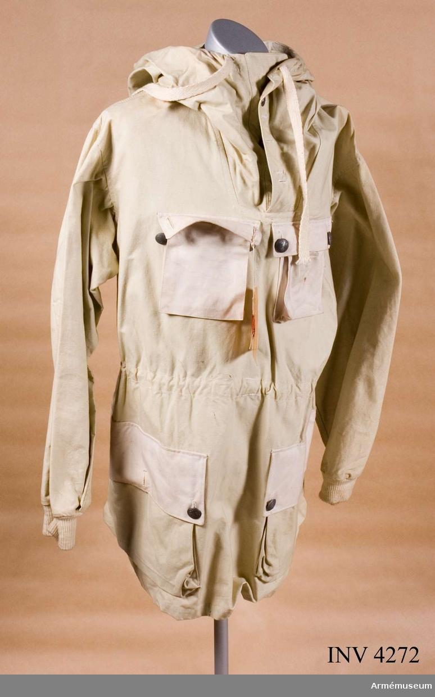 """Förslag t skidlöparblus typ II. År 1950 framlades förslag t ny skidlöparblus. Framtagen av KAFI Kungl Arméförvaltningens intendenturdepartement. Av kraftig, impregnerad bomullsväv. Två påsydda sidfickor knäppta m tre knappar. Två påsydda bröstfickor av mindre storlek, knäppta m två knappar. Alla fickor m bälg. Raka ficklock knäppta m t uniformsknappar m/1939 tre kronor på räfflad botten. I övrigt se AM 4271. Märkt på huvans V insida m vävd etikett """"ÖSB Militär Utrustnigar Örebro Sport- & Bilekipering, Örebro"""". På insidan i nacken vid halslinningen äganderättsmärkning m stämpelfärg: tre kronor. Någon ny snödräkt fastställdes inte förrän 1962."""