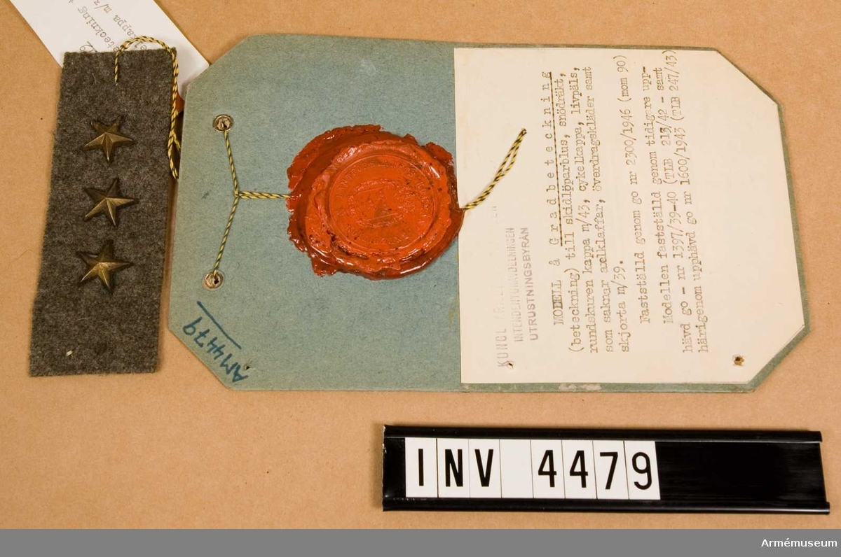 """I form av stjärna, stjärnknapp eller stolpe m/39 anlades på ett  rektangulärt underlag av gråbrungrön kommiss, som sedan  faststyddes på bröstets V del. Vidhängande etikett anger fastställelsedag: """"Stockholm Slott den 9.april 1942 Per Edvin Sköld / Henry Kellgren""""."""